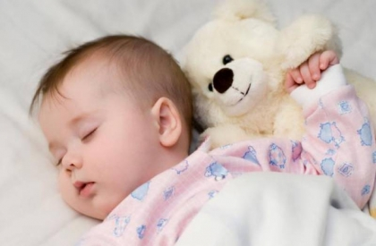 новорожденный сладко спит с игрушечным медвежонком
