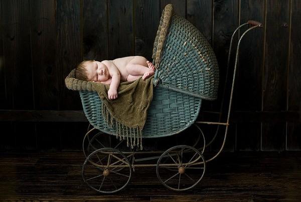 младенец дремлет в плетенной коляске
