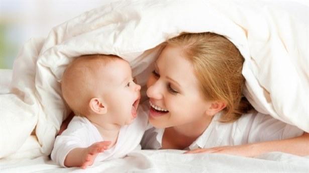 мама и малыш играют под одеялом