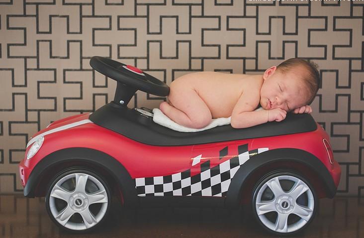 маленький ребенок дремлет на игрушечной красной машинке