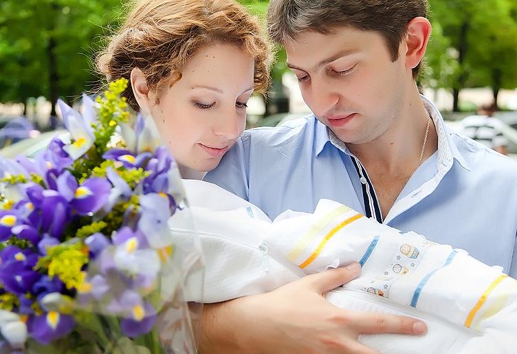 выписка из роддома летом: мама и папа с новорожденным на руках