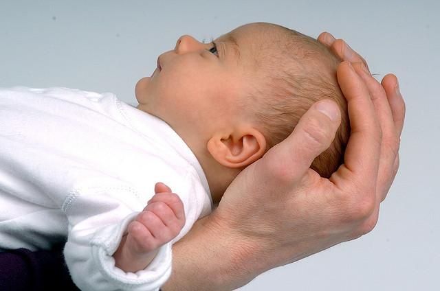 новорожденный на руках расслабленно лежит