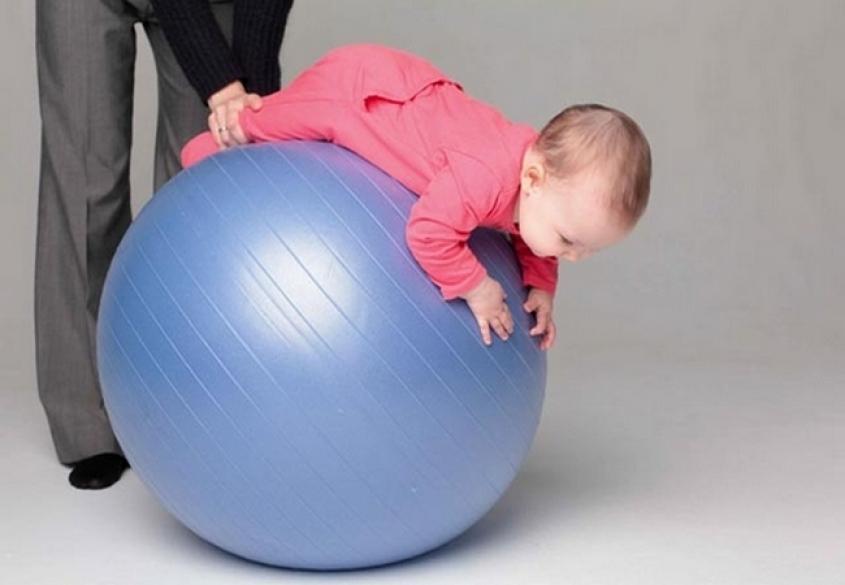 ребенок на животе качается на фитболе