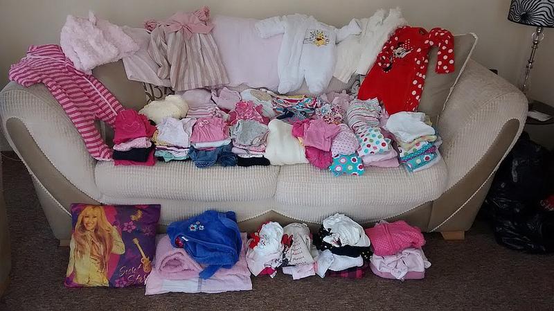 вещи для новорожденного, разложенные на диване