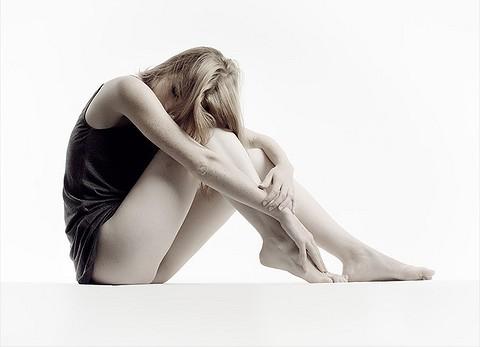 девушка на белом фоне сидит, держась за колени