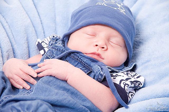 новорожденный малыш спит в синей шапочке