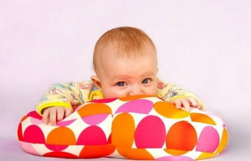 младенец держится за разноцветную подушку