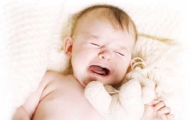 плачет новорожденный малыш, обнявши игрушку