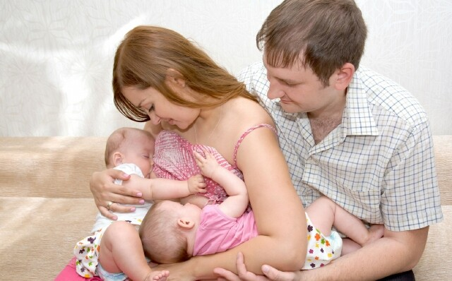 мама кормит грудью двойню, рядом помогает муж