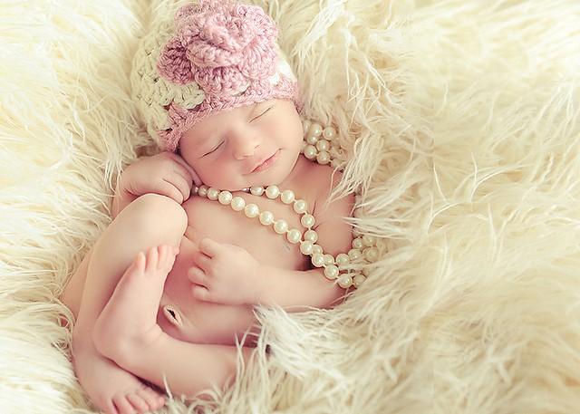 улыбается малышка с бусами во время сна