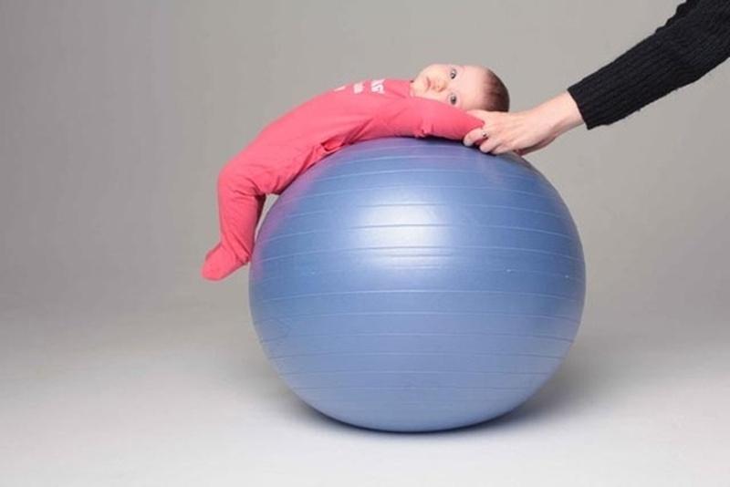 ребенок на спине качается на фитболе